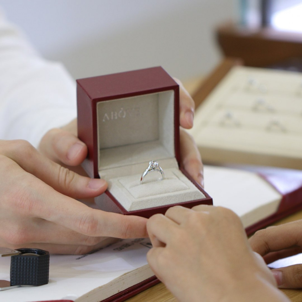 man opening ring box with engagement ring to woman