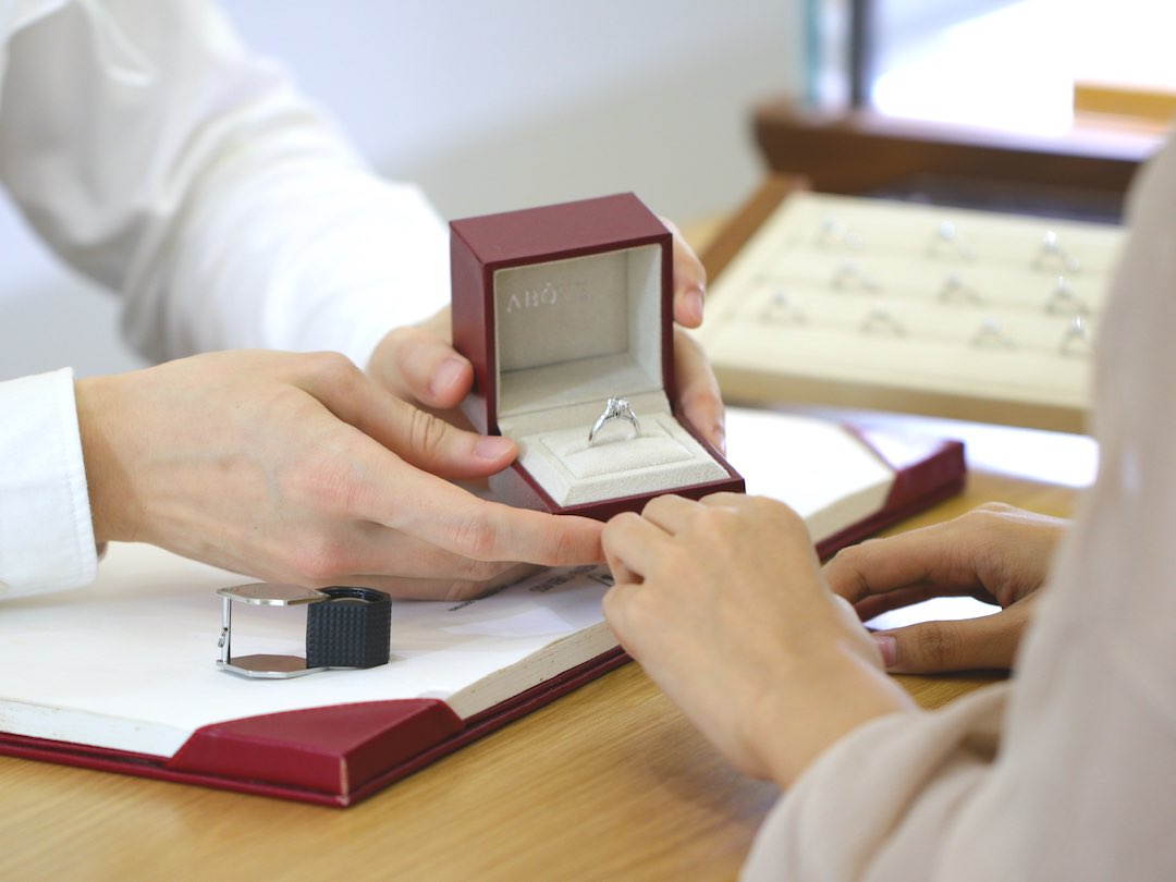 sales clerk holding diamond ring box with diamond ring inside to customer in diamond jewelry store