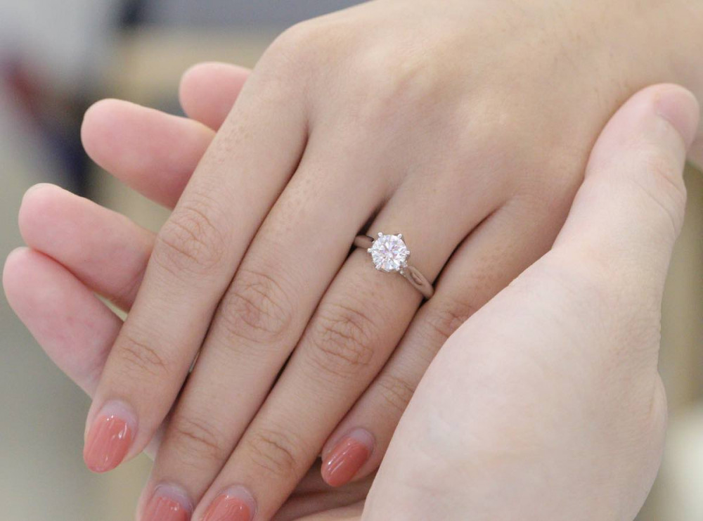 couple hand wearing diamond engagement ring