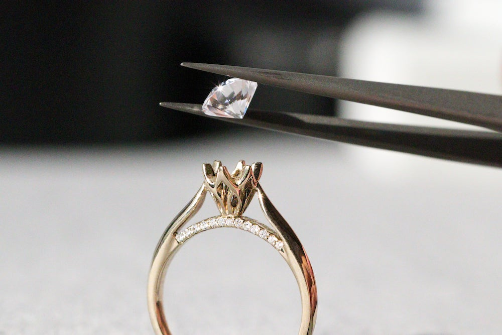 center diamond being set on a solitaire ring